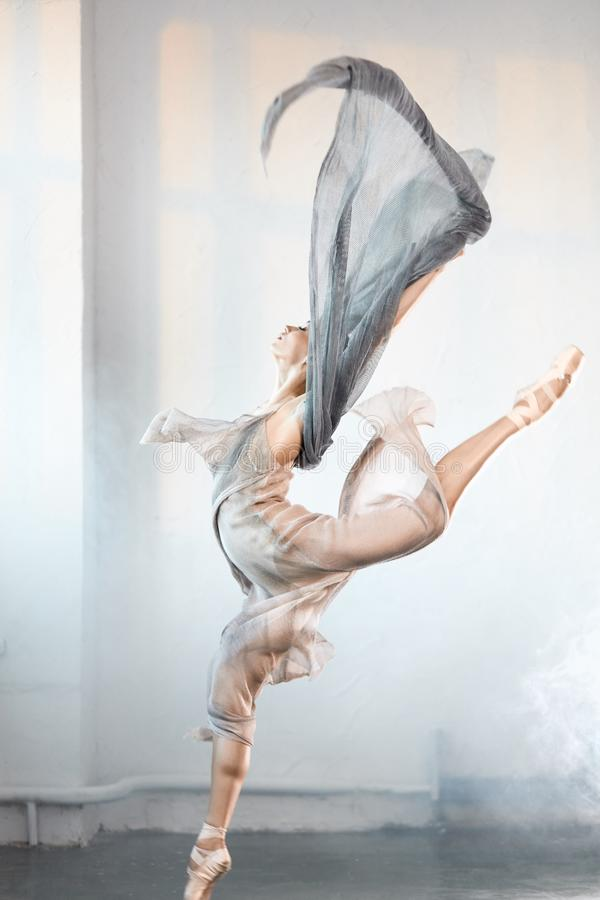 Ballerina wearing grey transparent clothes jumping on stage with smoke effect. Young ballet dancer wearing blue-grey transparent clothes and pointe has stock image