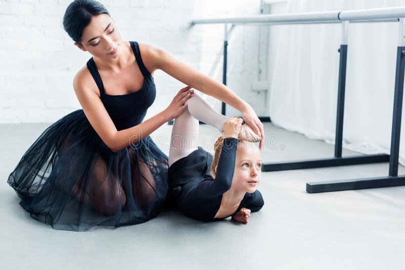 young ballet teacher and cute little student exercising together stock photo