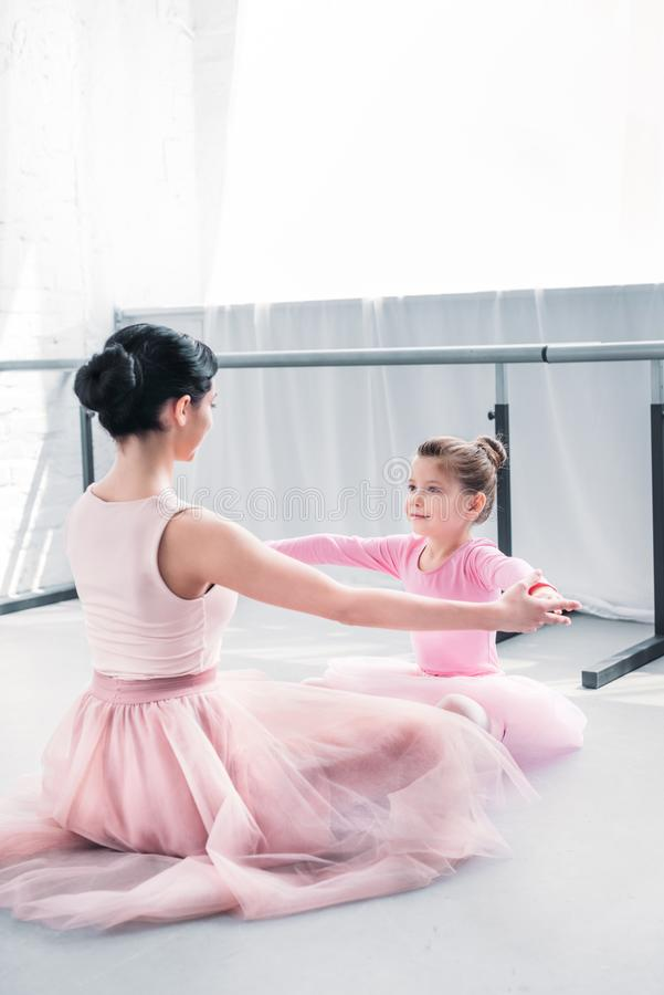 young ballet teacher and little student in pink tutu skirts training together royalty free stock photo