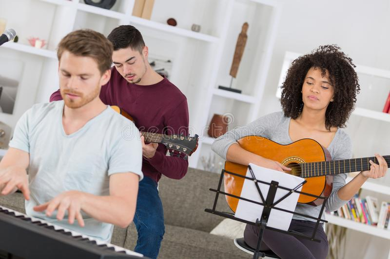 Young band group rehearsing for gig stock photo