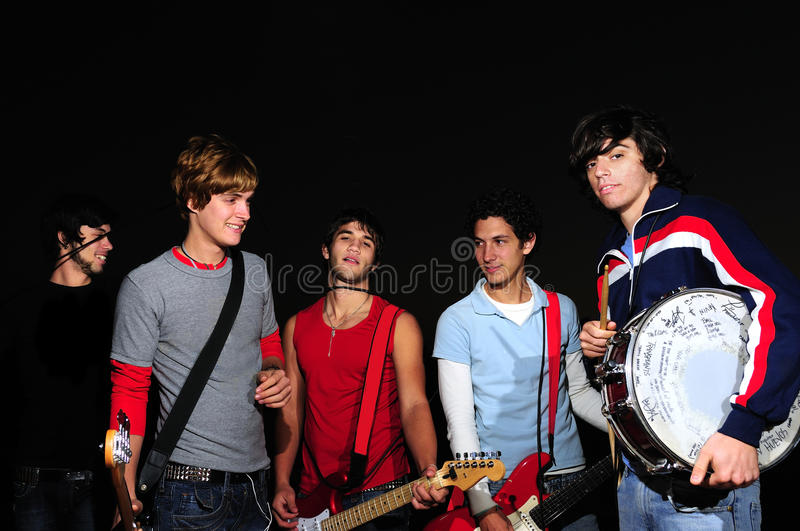 Young band posing with instruments. Portrait of young musical band posing with instruments over black stock photography