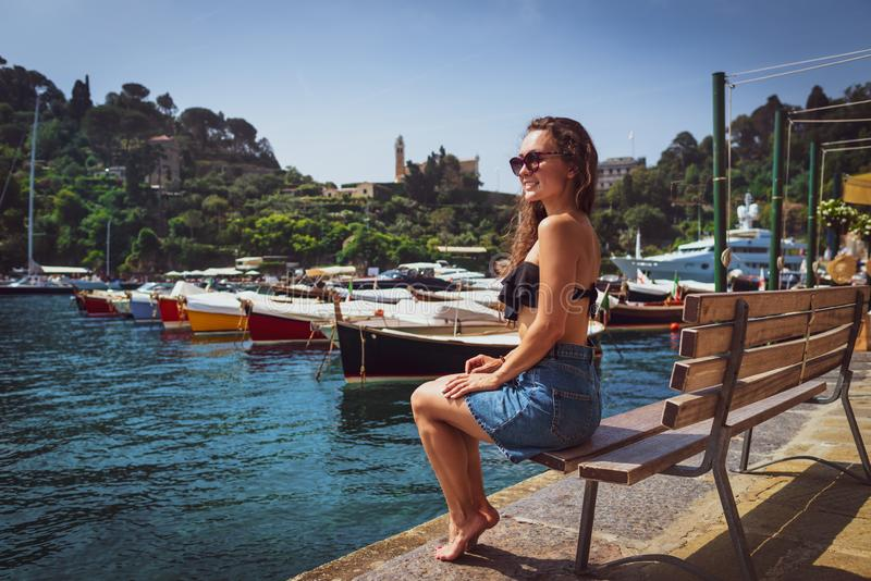 Young barefoot woman sitting on bench in marina stock photos