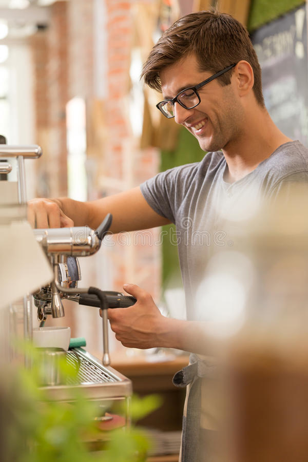 Young barista preapering cup of coffee. Shot of a young barista preparing cup of coffee in a coffee house royalty free stock photos