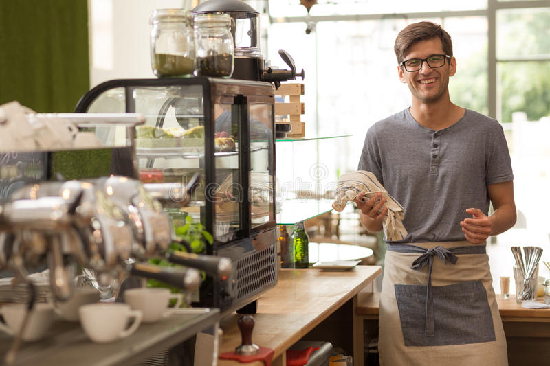 Young barista standing in his coffee house. Shot of a young barista standing in his coffee house and smiling at the camera stock images