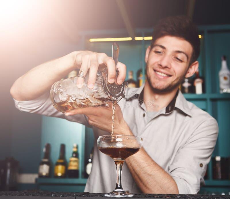 Young Barman mixing cosmopolitan cocktail royalty free stock images