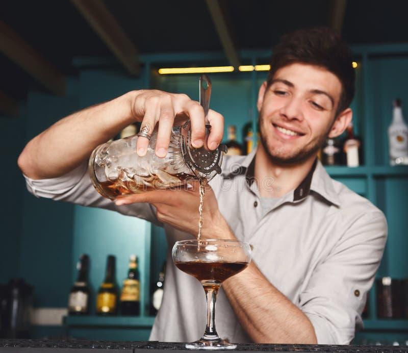 Young Barman mixing cosmopolitan cocktail stock photos