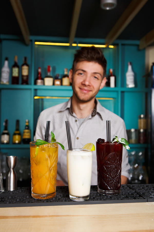 Young Barman offers alcohol cocktails in night club bar stock photography