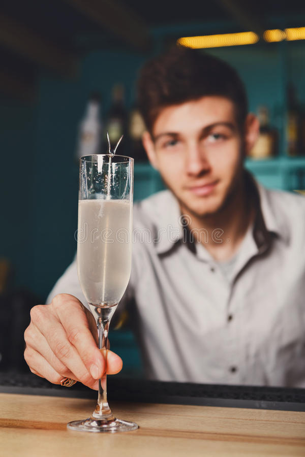 Young Barman offers champagne glass in night club bar royalty free stock photos