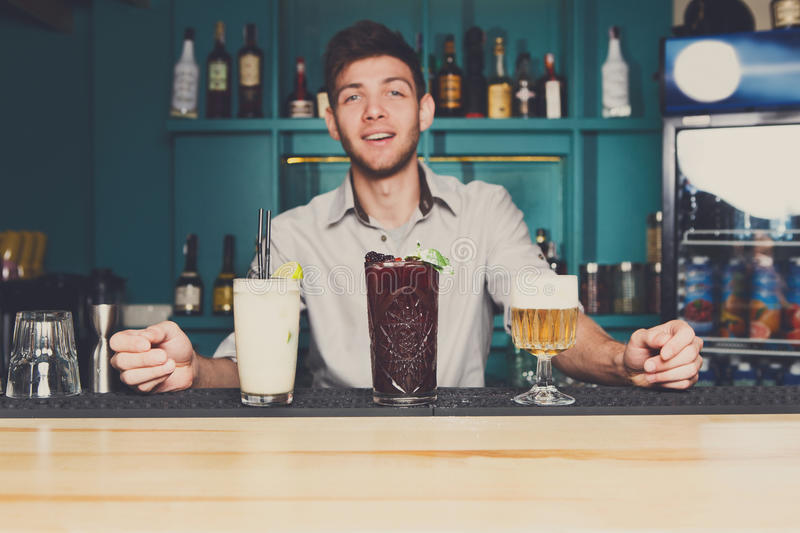 Young Barman offers cocktails in night club bar royalty free stock photos