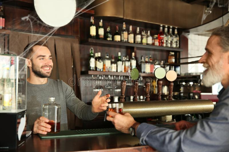 Young barman serving client in pub stock image