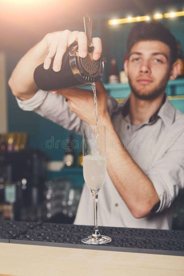 Young bartender pouring cocktail drink into glass royalty free stock images