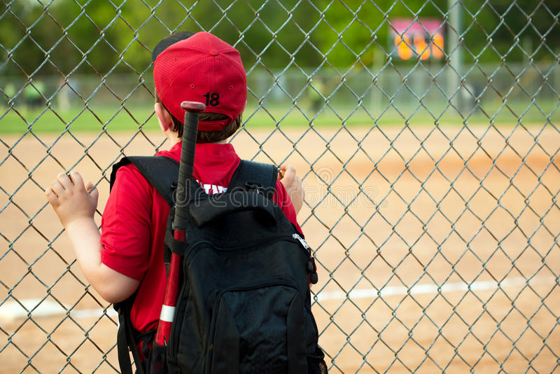 Young baseball player watching game. From outside fence royalty free stock image
