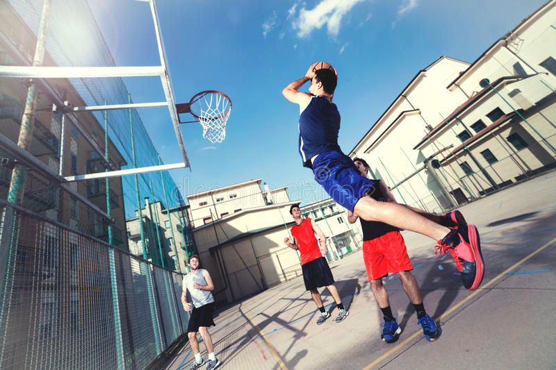 Young basketball players playing with energy in a urban place stock image
