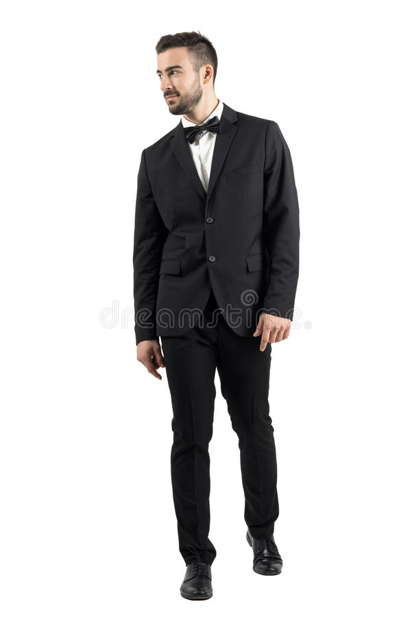 Young beaded man in tuxedo with bow tie walking towards the camera looking away royalty free stock images