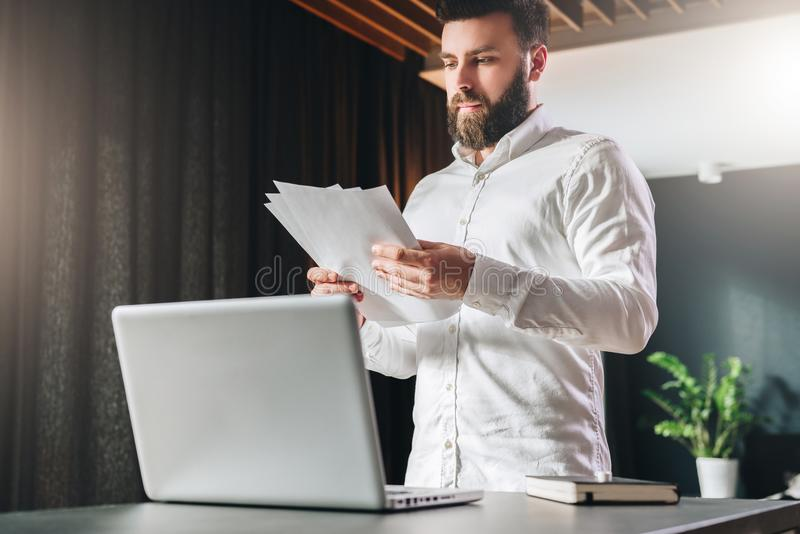 Young bearded atrractive businessman in white shirt is standing near desk in front of laptop, reading documents. stock image