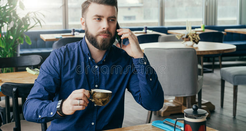 Young bearded attractive businessman sitting at wooden table in restaurant, talking on phone and drinking tea. stock image