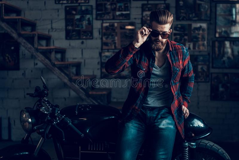 Young Biker in Sunglasses on Motorcycle in Garage. stock image