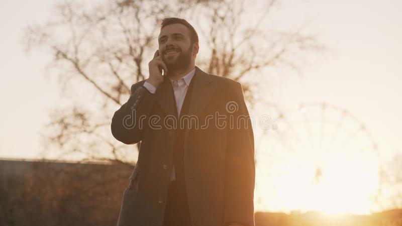 Young bearded business man in coat talking at smartphone and making deals on street with sunlight backlit in evening stock images