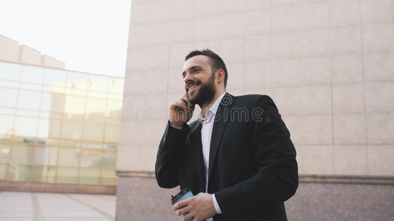 Young bearded business man talking on cell phone making deals with cup of coffee near modern office buildings stock photography