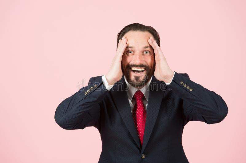 Aged bearded businessman acting surprised with hands on head wide opened mouth isolated on pastel pink wall. Face happy emotion. stock photography