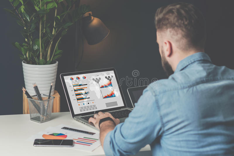 Young bearded businessman in denim shirt is sitting in office at table and is using laptop with charts, graphs. Back view. Young bearded businessman in denim stock photo
