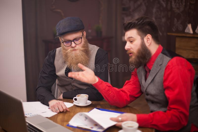 Young bearded businessman showing presentation on his laptop to his business partner. stock photos