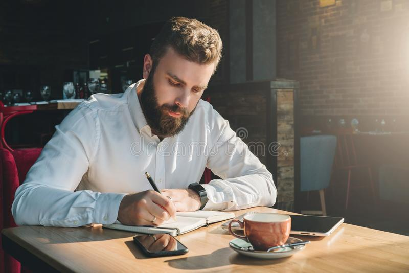 Young bearded businessman sits in cafe, home at table and writes in notebook. On table tablet computer, smartphone. Man is working, planning.Online education stock images
