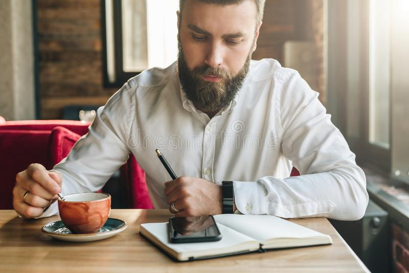 Young bearded businessman, sits in cafe, office at table, holds pen in his hand, reads information on smartphone screen stock image