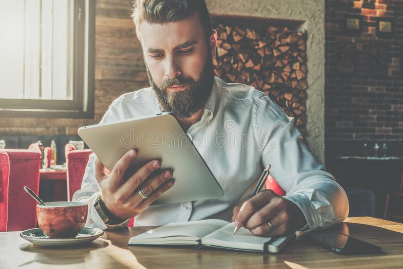 Young bearded businessman sits in cafe at table, holding tablet computer and writes in notebook. Man is working stock photography