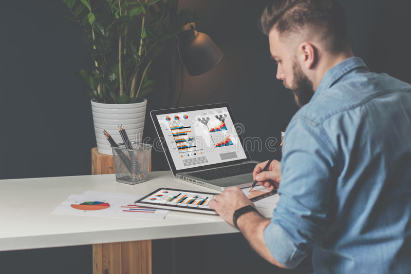 Young bearded businessman sits in office at table,using digital tablet and explores charts,making notes. royalty free stock images