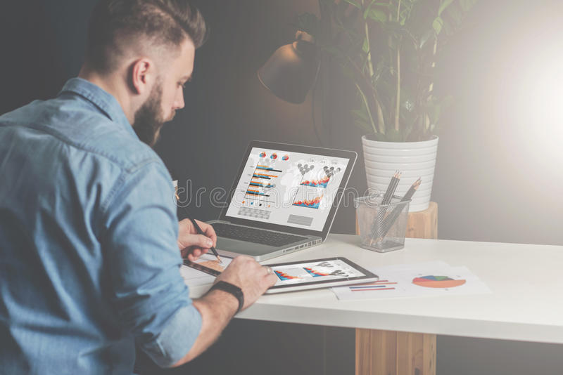 Young bearded businessman sits in office at table,using tablet computer and explores charts,making notes. royalty free stock photo