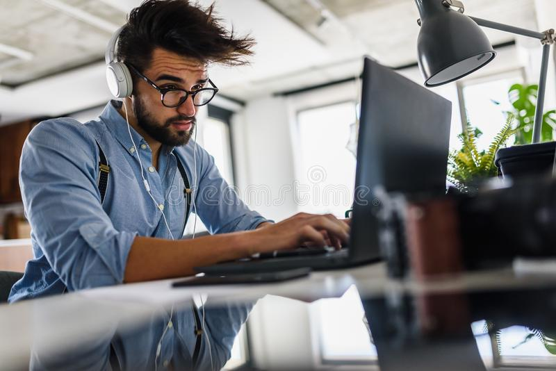 Young bearded businessman is sitting in front of computer, working. Freelancer, entrepreneur works at home. royalty free stock photo