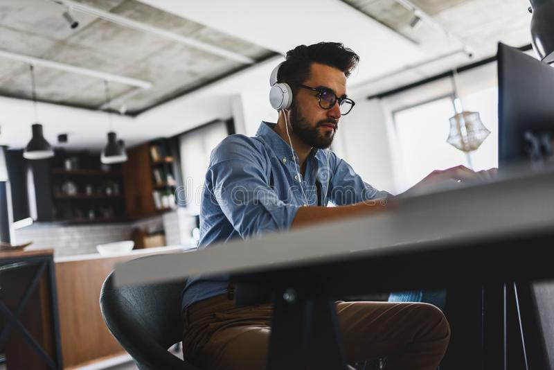 Young bearded businessman is sitting in front of computer, working. Freelancer, entrepreneur works at home. stock photography