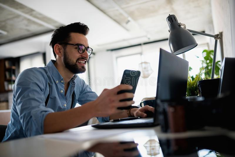 Young bearded businessman is sitting in front of computer, working. Freelancer, entrepreneur works at home. royalty free stock images