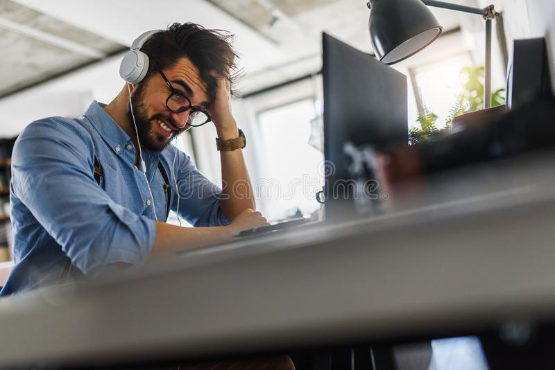 Young bearded businessman is sitting in front of computer, working. Freelancer, entrepreneur works at home. royalty free stock photography