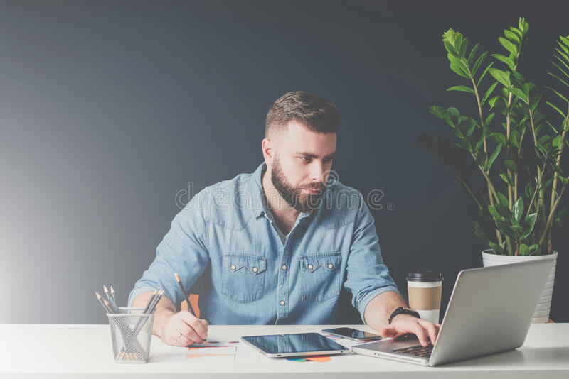 Young bearded businessman is sitting in office at desk, working and is using laptop while making notes on paper. stock images