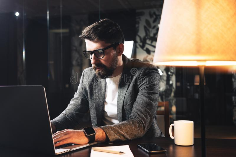 Young bearded businessman sitting at wooden table with lamp in loft office at night. Project manager working process and typing te stock image