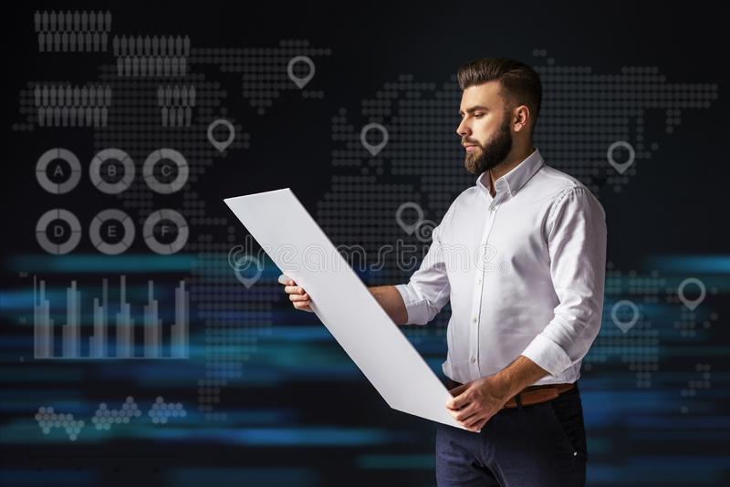 Young bearded businessman standing and holding tablet. Virtual world map with icons of points, graphics, diagrams royalty free stock photo