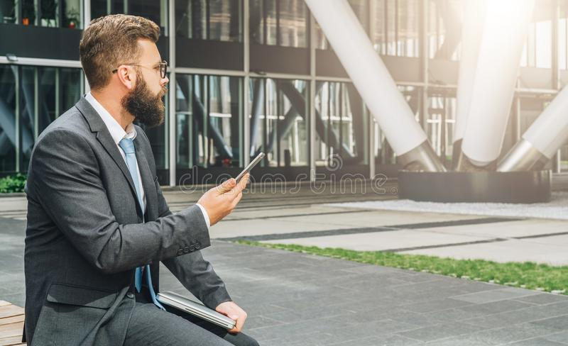 Young bearded businessman in suit and tie sitting in park on bench, holding closed laptop and using smartphone stock photography