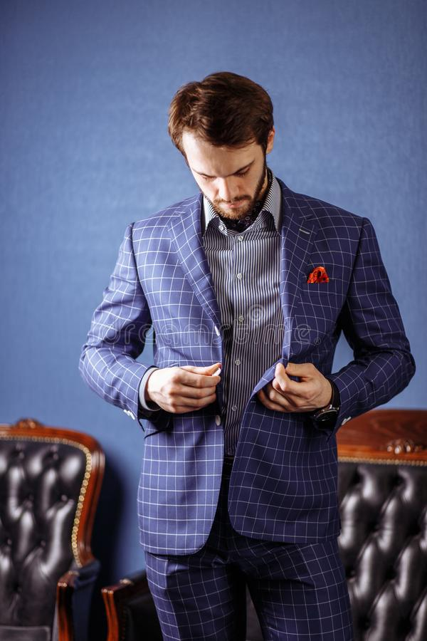 Young bearded businessman trying on custom tailored suit, buttoning jacket stock image