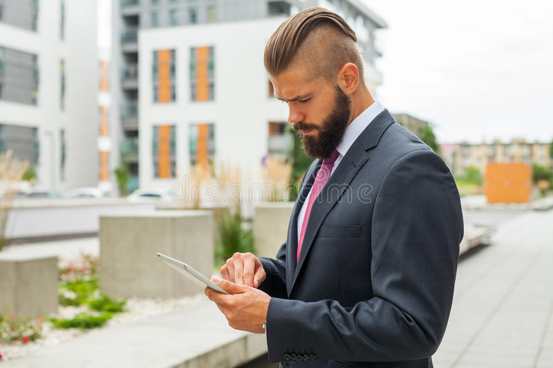Young bearded businessman writting business e-mail using his tablet. Pc. Outdoor photo royalty free stock images