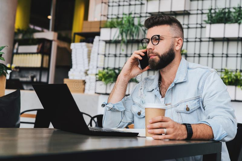 Young bearded cheerful man sits at table in front of laptops, talking on mobile phone while making notes in notebook. royalty free stock images