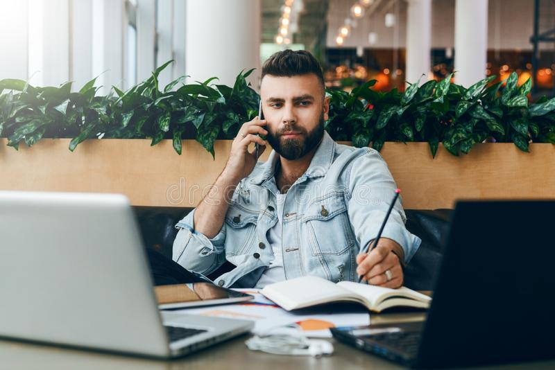 Young bearded cheerful man sits at table in front of laptops, talking on mobile phone while making notes in notebook. royalty free stock photos