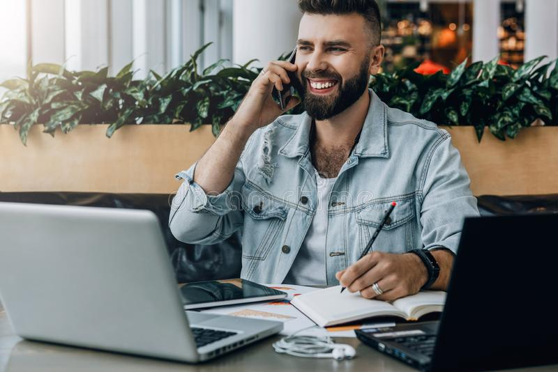 Young bearded cheerful man sits at table in front of laptops, talking on mobile phone while making notes in notebook. stock photo
