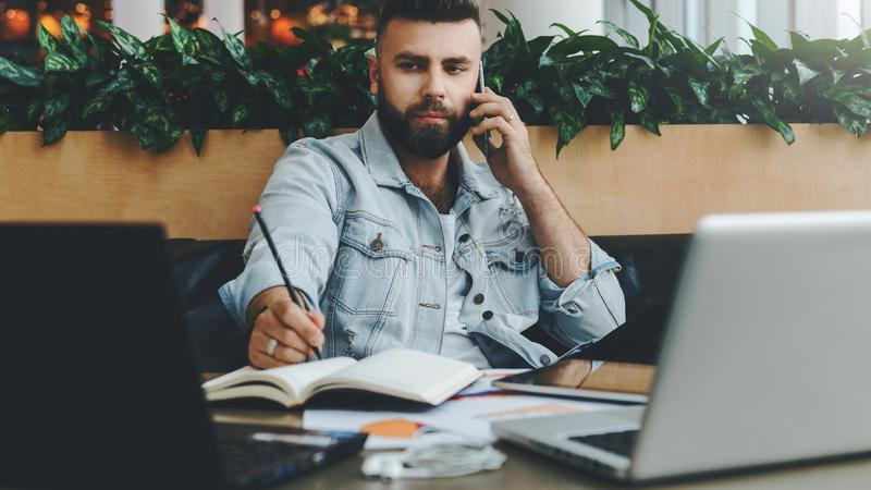 Young bearded cheerful man sits at table in front of laptops, talking on mobile phone while making notes in notebook. royalty free stock photography
