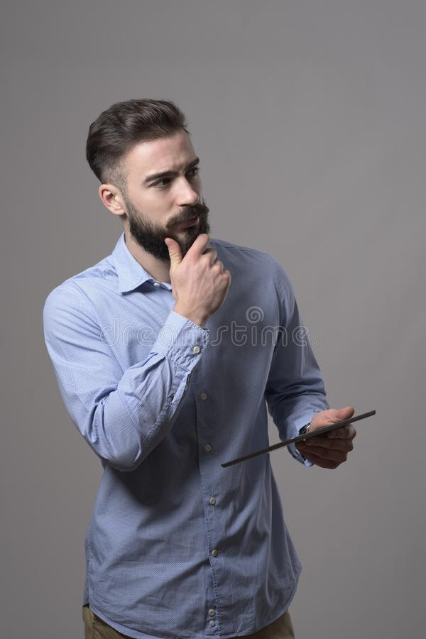 Young bearded concentrated adult business man holding tablet computer thinking and touching beard looking away at copyspace stock photos