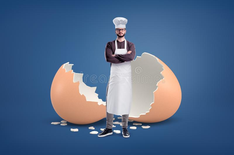 A young bearded cook in a white apron and a hat stands near a large broken egg shell. royalty free stock image