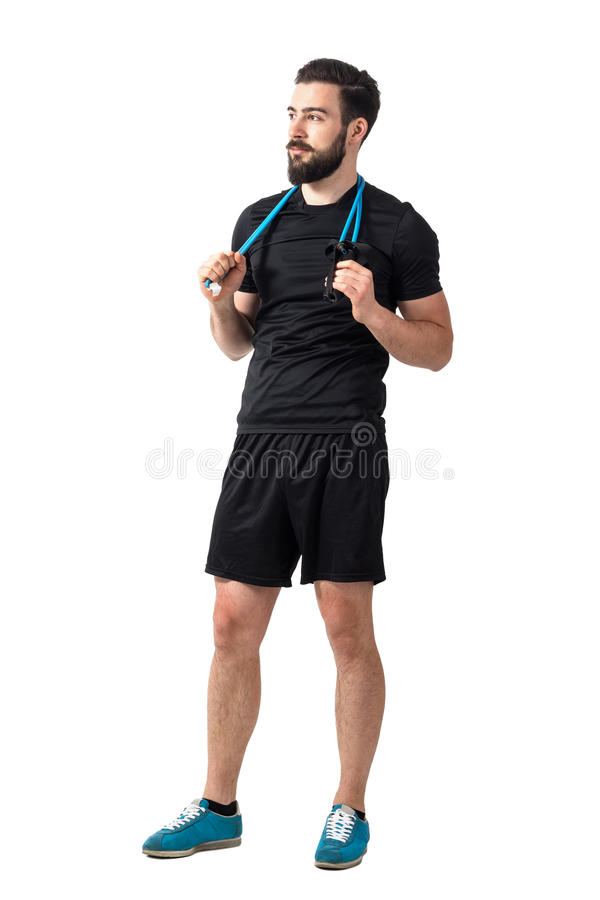 Young bearded fitness model relaxing with resistance bands around neck looking away stock image