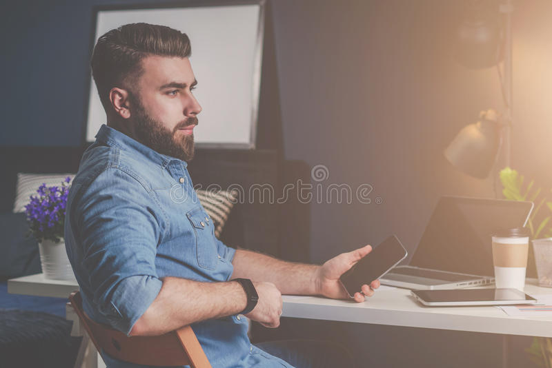 Young bearded freelancer man in denim shirt is sitting at home at table, holding mobile phone in his hand and thinking. On desk is laptop,tablet computer and stock images