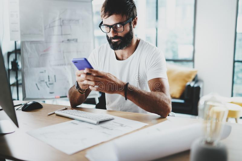 Young bearded graphic designer wearing eye glasses and working at modern loft studio-office.Man using smartphone.Blurred royalty free stock image